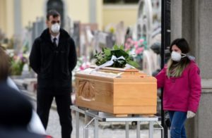 A teenage girl wearing a face mask touches the coffin of a deceased relative during a funeral ceremony at the entrance of the small cemetery of Bolgare, Lombardy, on March 23, 2020 during the country's lockdown aimed at stopping the spread of the COVID-19 new coronavirus pandemic. (Photo by Piero CRUCIATTI / AFP)